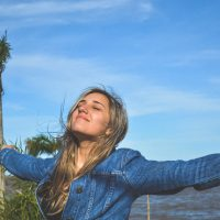 woman with outstretched arms by beach